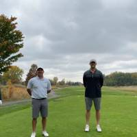 Four alumni taking picture on golf course